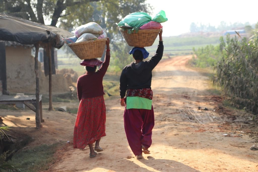 Two people walk on the village road carrying baskets on their head