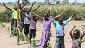 Children stand next to tree seedlings.