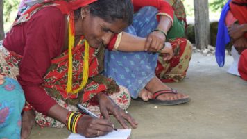 Panna Devi sits on the ground and writes with a pencil and a paper